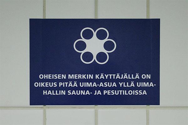 Impivaaran uimahallin asiakkaat saavat informaatiota käyttöoikeusmerkistä suihkutilassa olevasta tarrasta. Kuva: Tiina Rastiola