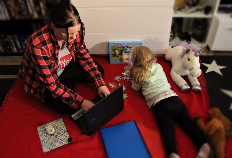 Henriikka keskittyy läksyihin tyttären leikkiessä vieressä.
