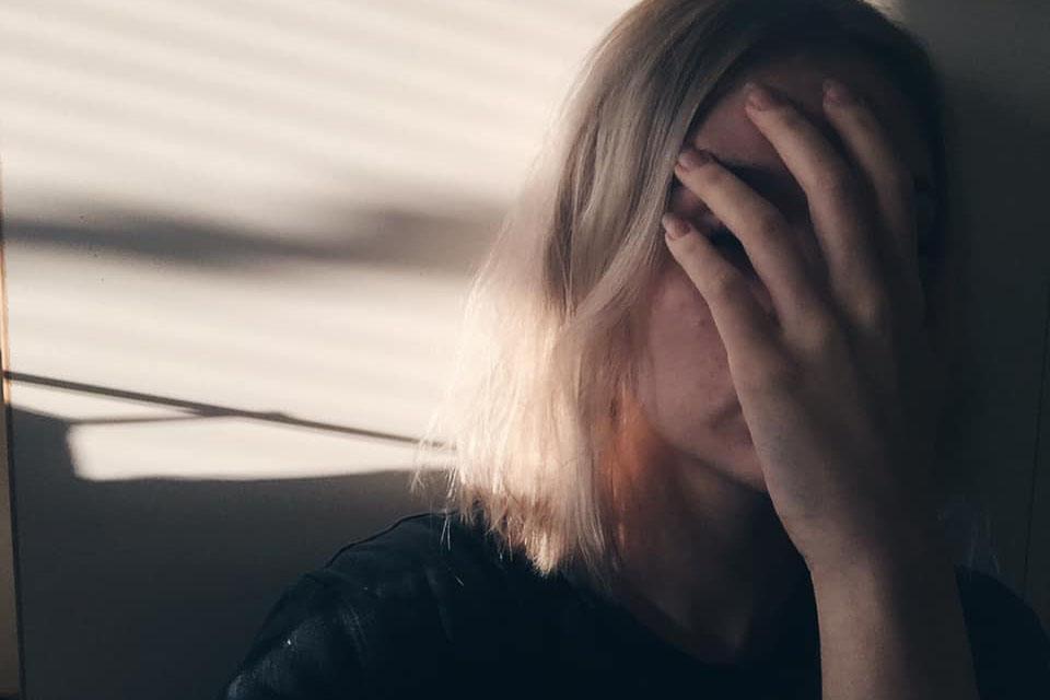 Naisella on käsi kasvojen edessä.