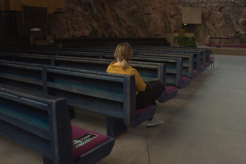 Nainen istumassa Temppeliaukion kirkossa