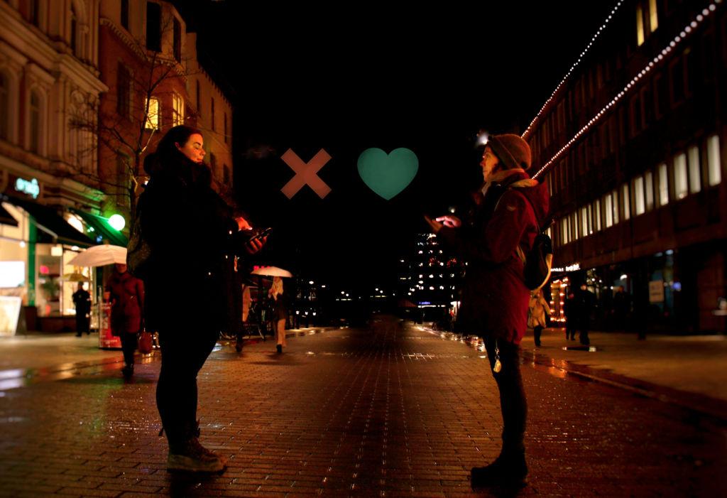 Kaksi ihmistä kohtaa pimeällä kadulla. Heidän välillään loistavat Tinderistä tutut ruksi ja sydän.