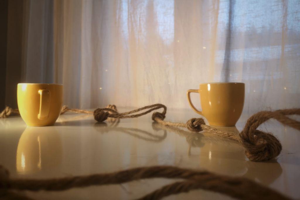 Kuvassa solmuinen köysi kiertää kahta kahvikuppia valkoisella pöydällä. Taustalla verhojen takaa kuultaa kerrostalomaisema.
