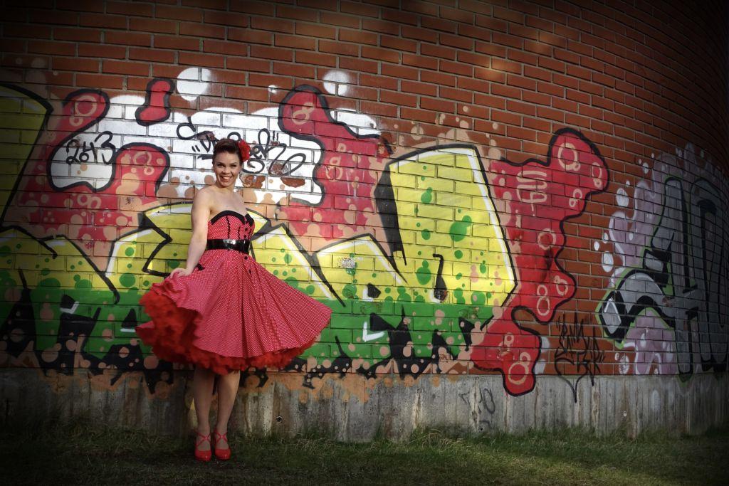 Nainen seisoo pin-up mekko päällä graffitiseinää vasten