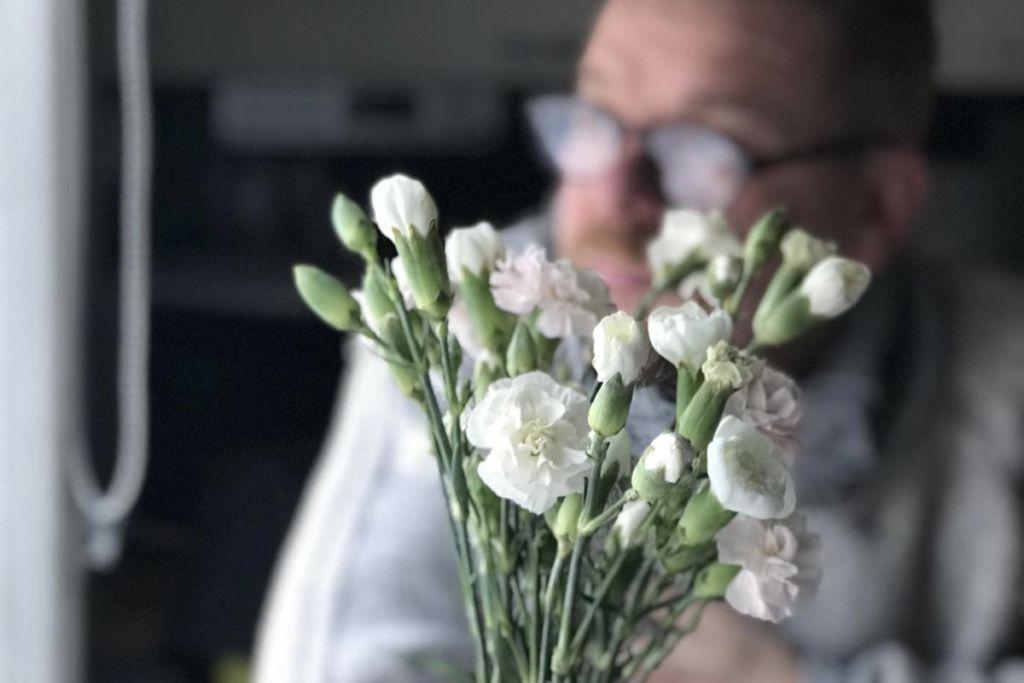 Ihminen katsoo ikkunasta ulos kukkakimpun takana.