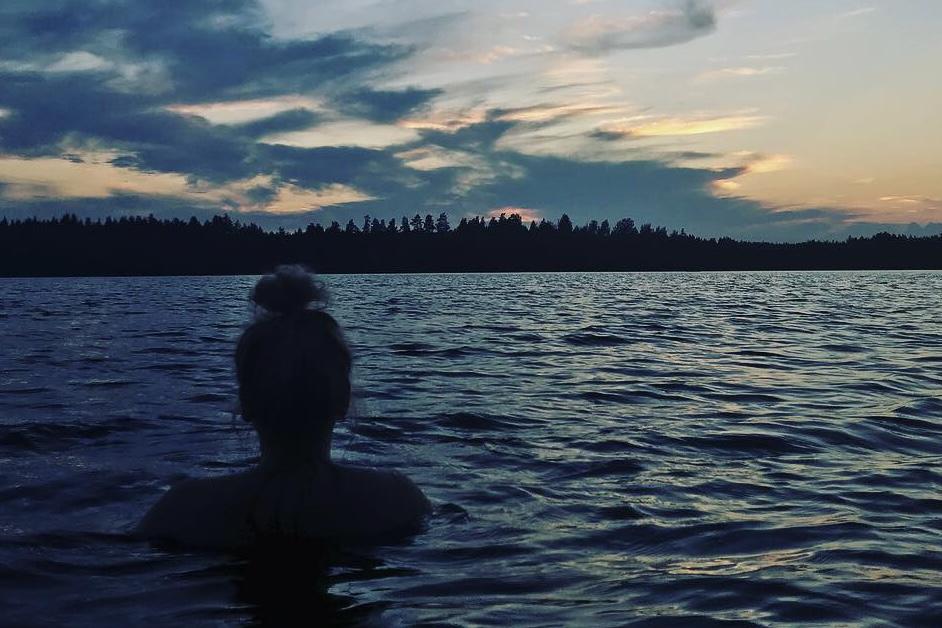 Ihminen katsoo järvelle synkässä maisemassa.