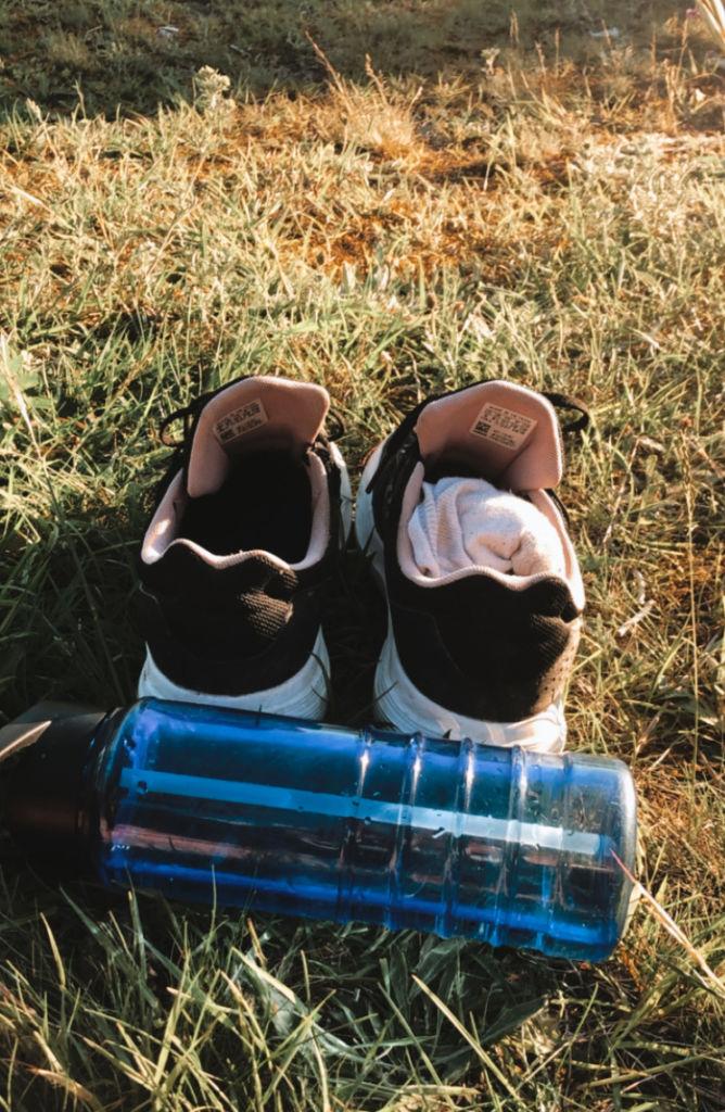Kengät ja juomapullo ruohikolla.