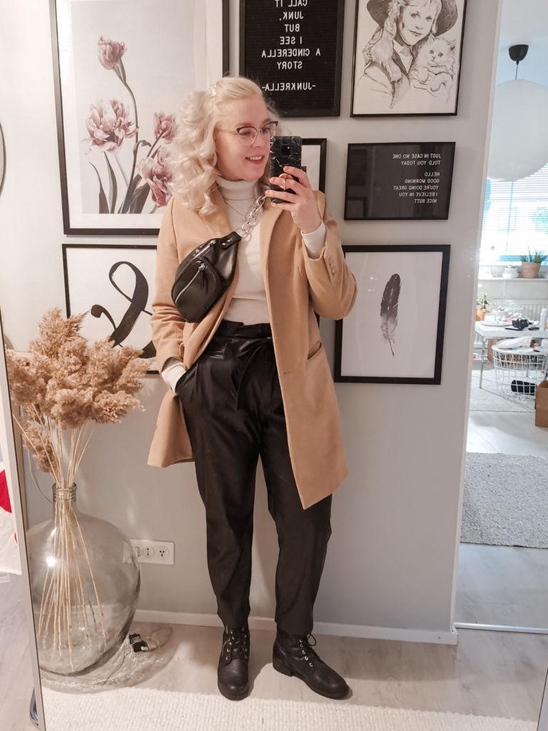 Heidi Haapalan omakuva peilin kautta otettuna. Kuvassa hänellä on vaalea takki ja mustat housut. Taustaseinällä on tauluja.