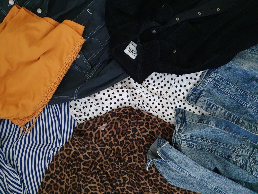 Erilaisia kirpputoreilta ostettuja vaatteita kasassa