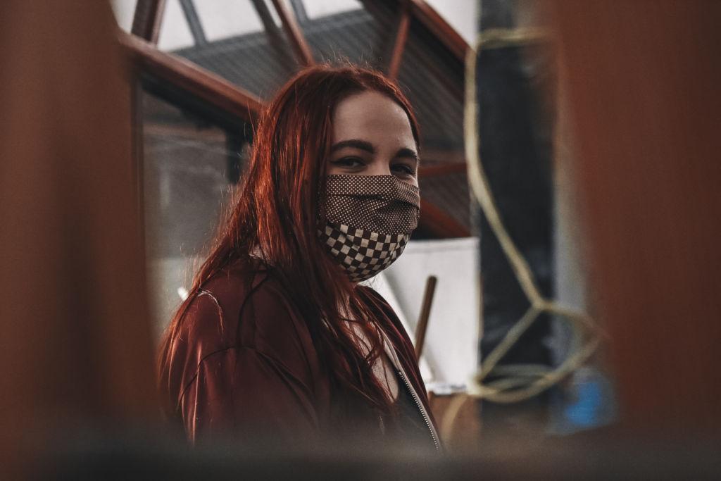 punahiuksinen nainen, jolla on ruskea maski kasvoilla