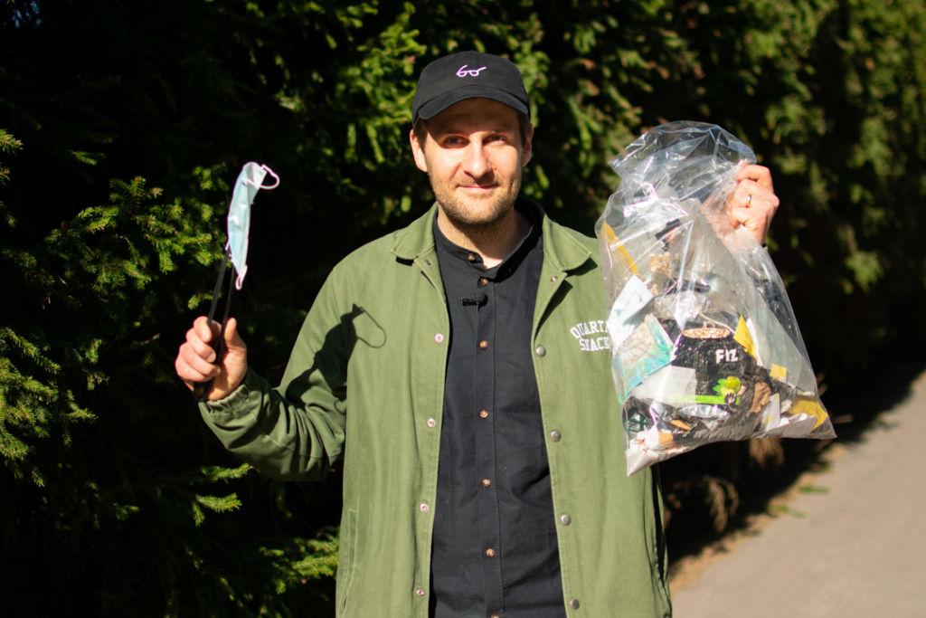 Mies seisoo keskellä kuvaa. Hän näyttää oikeassa kädessään pitelemäänsä kasvomaskia ja vasemassa kädessään olevaa roskapussia täynnä roskia.