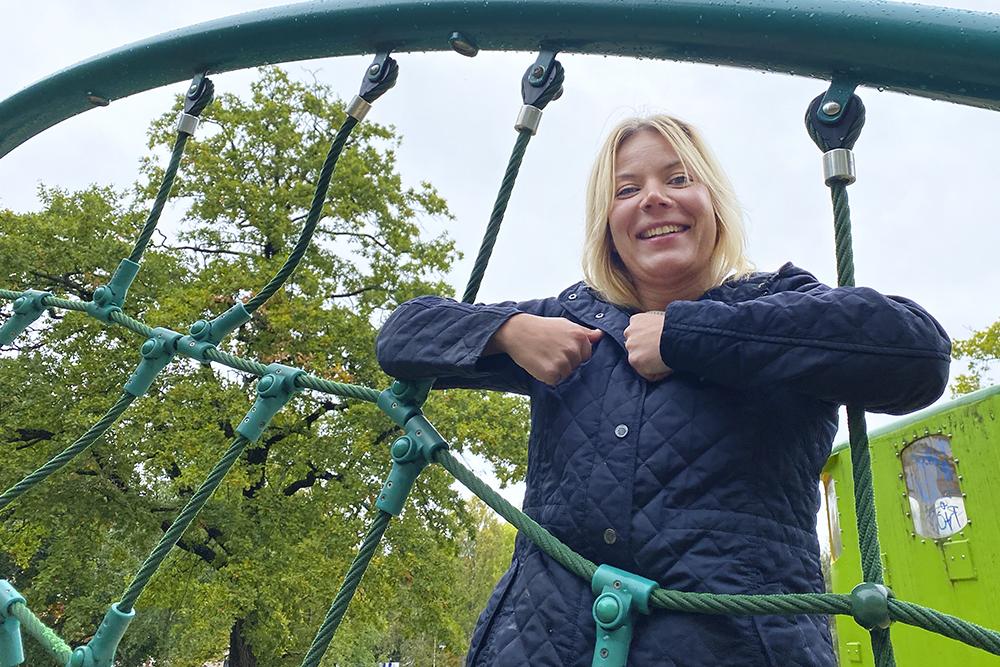 Nainen on kiivennyt kiipeilytelineeseen leikkipuistossa ja hymyilee kameralle.
