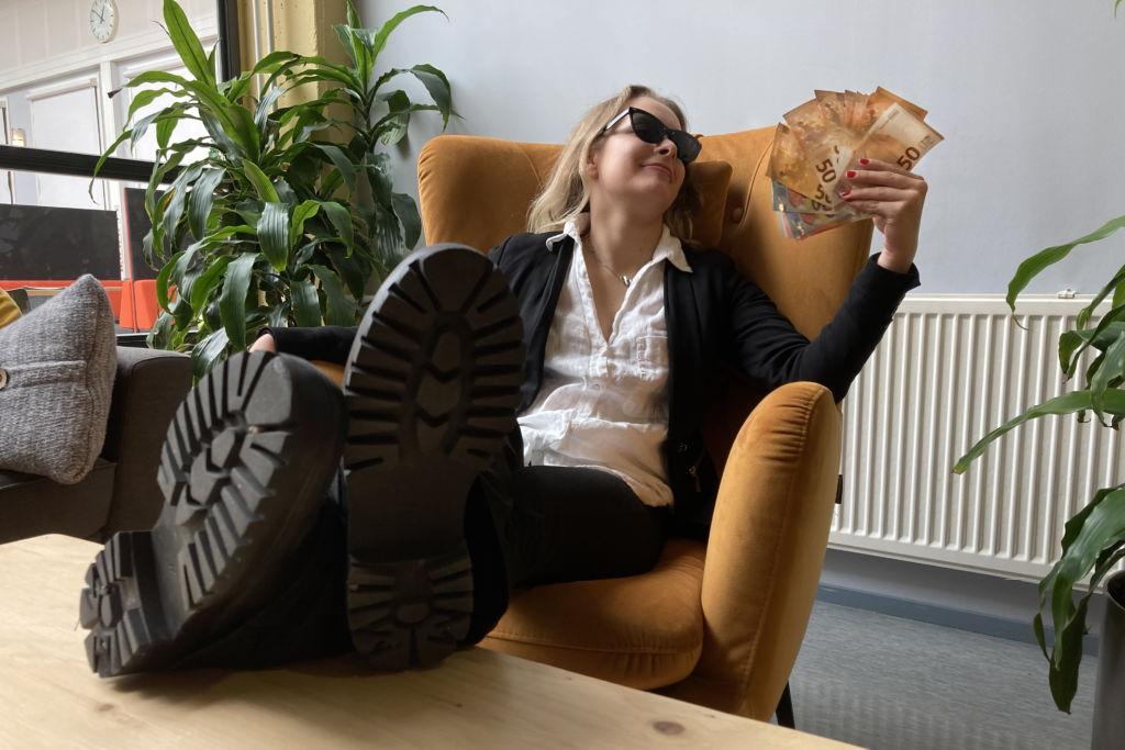 Nuori nainen istuu reteästi nojatuolilla jalat pöydällä, aurinkolasit päässä , jalat pöydällä ja pitää kädessään seteliviuhkaa