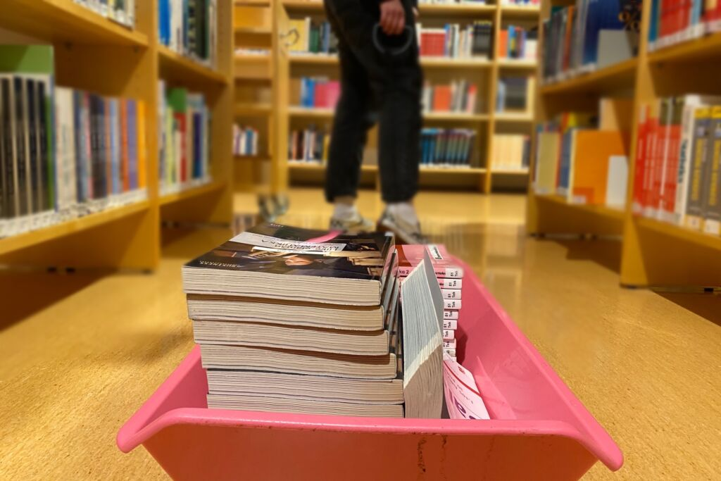 Ihminen vetää perässään pulkkaa, jossa on kirjoja kirjastossa.